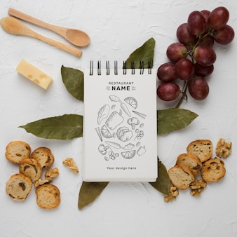 Composizione di deliziosi alimenti con notepad mock-up