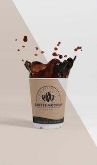 Composizione della tazza di caffè in carta con spruzzi di caffè