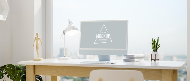 Computer devices with mockup screen and decorations on the desk beside glass wall window