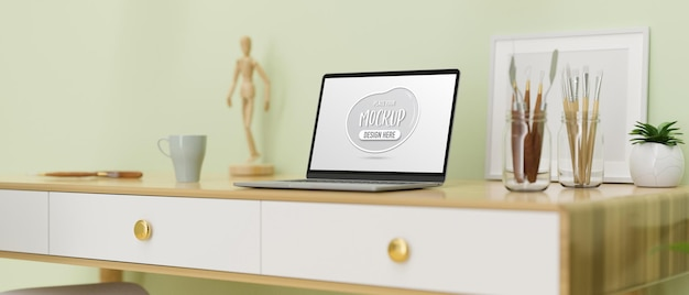 Computer laptop with mockup screen on the desk with paint tools and decorations 3d rendering
