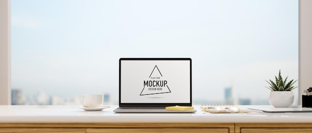 Computer laptop with mockup screen on the desk with panoramic window