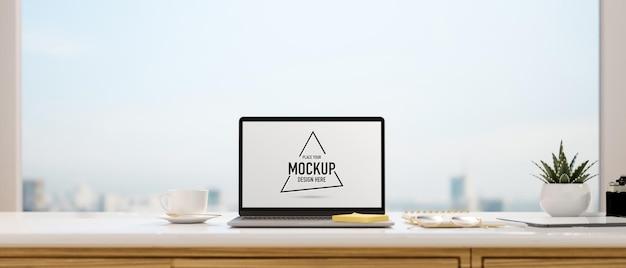 탁 트인 창문이있는 책상에 모형 스크린이있는 컴퓨터 노트북