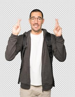 Обеспокоенный студент делает жест скрещенными пальцами