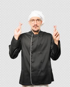 Обеспокоенный молодой шеф-повар делает жест скрещенными пальцами