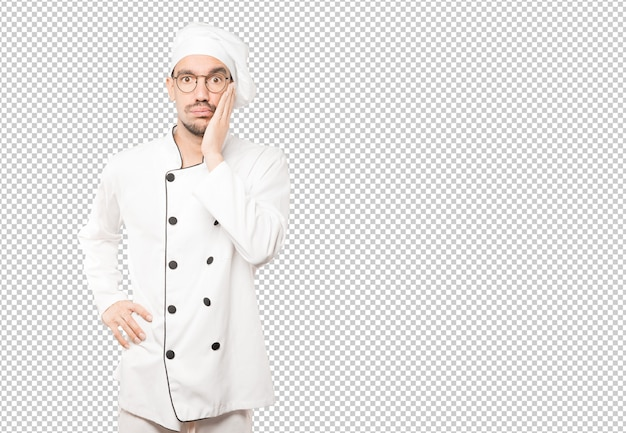 Concerned young chef posing against background