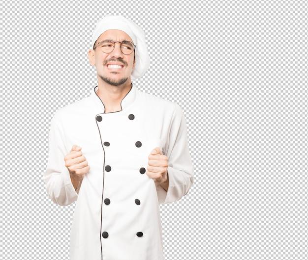 Обеспокоенный молодой повар с жестом стресса