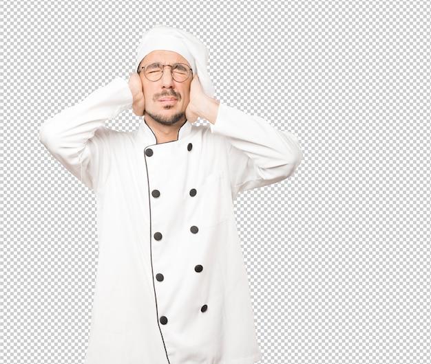 Обеспокоенный молодой шеф-повар обеспокоен громкими шумами и прикрывает уши