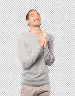 心配している若い男がジェスチャーを祈る