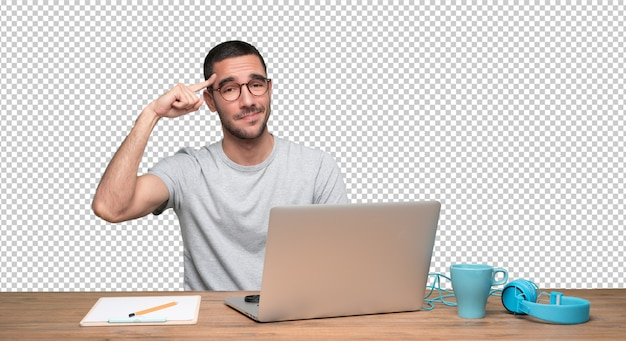 Concerned young man sitting at his desk with a gesture of concentration