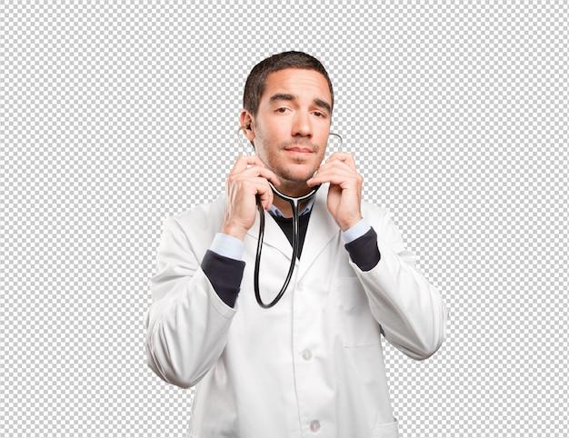 白い背景に聴診器を使用している自信のある医師