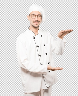 Confident young chef doing a gesture of holding something with his hands