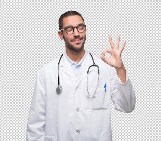 すべての権利のジェスチャーをしている自信のある若い医者