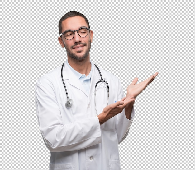 Confident young doctor showing something with his hands