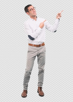 Confident young man pointing with his hand - concept of selling with an ad - full body shot