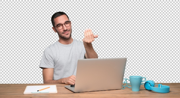 Confident young man sitting at his desk and doing a gesture of inviting with his hand