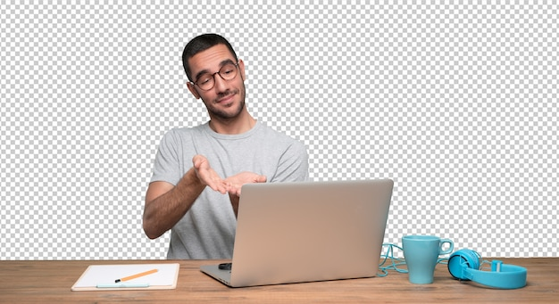 Confident young man sitting at his desk and showing something with his hands