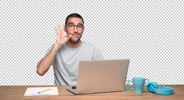 Confident young man sitting at his desk with a gesture of keeping a secret