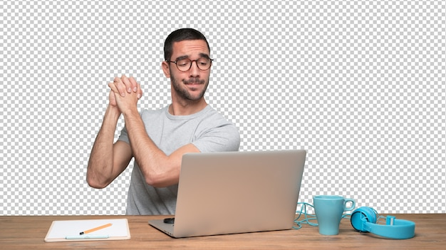 Confident young man sitting at his desk with a gesture of teamwork