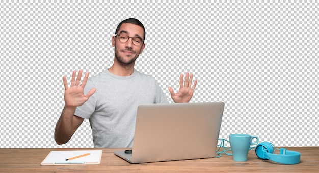 Confident young man sitting at his desk with a keep calm gesture