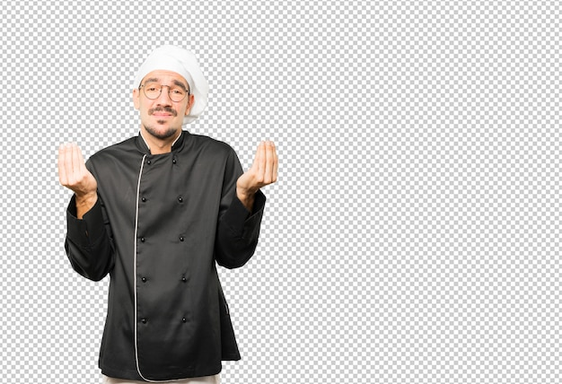 Confused young chef making an italian gesture of not understand