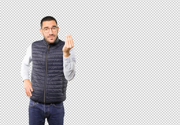 Confused young man making an italian gesture of not understand