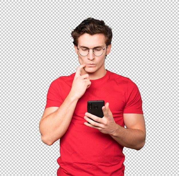 Смущенный молодой человек с помощью мобильного телефона