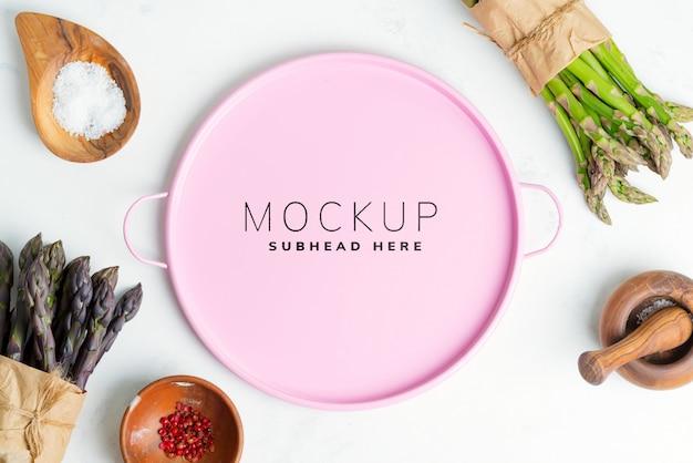 다른 양념과 분홍색 접시 모형과 함께 아스파라거스 야채 움큼으로 배경 요리