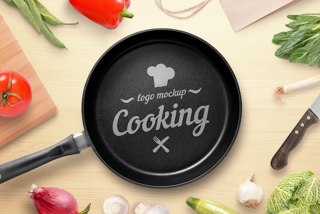 Cooking, restaurant logo mockup. pan on the kitchen table surrounded by vegetables. top view, flat lay