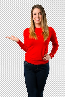 手のひらに想像上のcopyspaceを保持している若いブロンドの女性