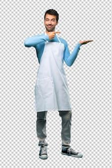 広告を挿入するために手のひらに想像上copyspaceを保持しているエプロンを着た男