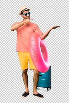 広告を挿入するために手のひらに想像上copyspaceを保持している彼の夏休みに帽子とサングラスを持つ男