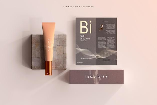 Mockup di tubo di crema cosmetica con brochure bifold