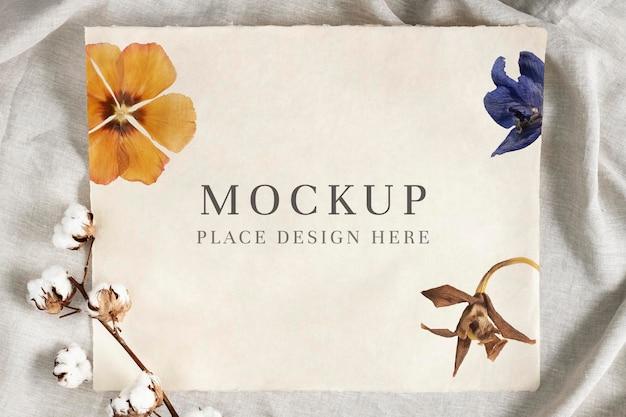 Ветка цветка хлопка на бумажном макете на помятом фоне серой ткани