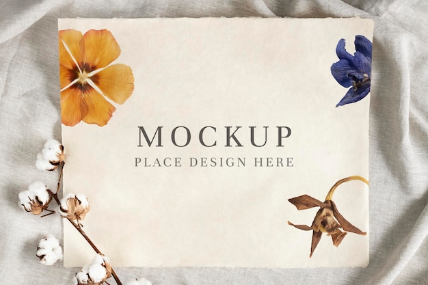 Cotton flower branch on a paper mockup over a creased gray fabric background