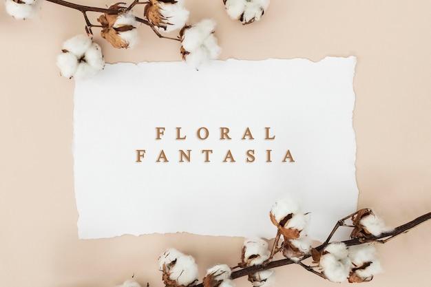 ベージュの背景に白いカードのモックアップと綿の花の枝