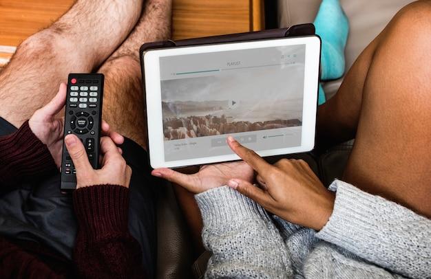 Пара проверяет музыкальный плейлист на планшете