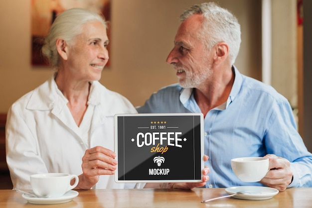 Couple in coffee shop holding mobile mock-up