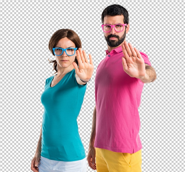 Couple in colorful clothes making stop sign