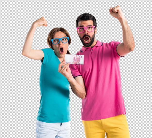 Couple in colorful clothes taking a lot of money