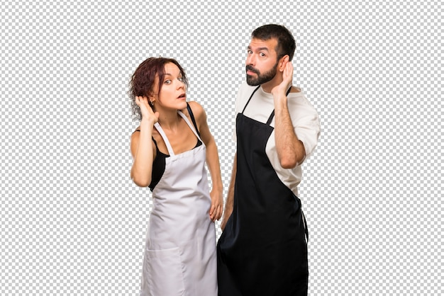 Couple of cooks listening to something by putting hand on the ear