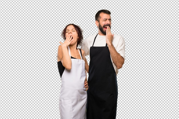 Couple of cooks yawning and covering mouth with hand. sleepy expression