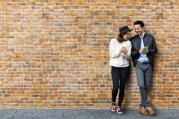 Couple dating in front of brick wall