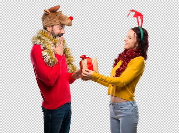 Couple dressed up for the christmas holidays holding a present