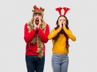 Couple dressed up for the christmas holidays shouting with mouth wide open and announcing something