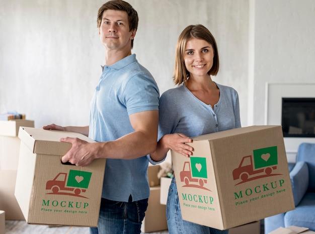 彼らの新しい家のために箱を持って幸せであるカップル