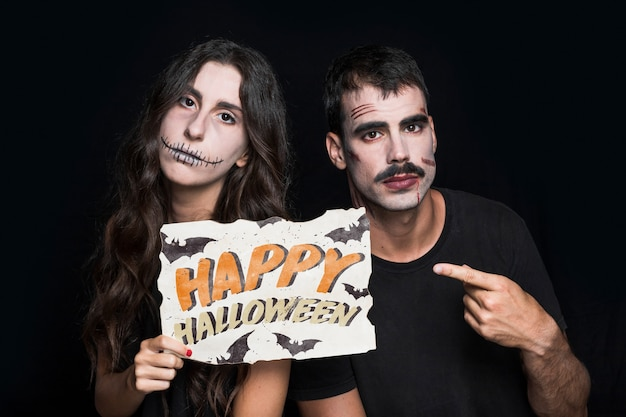 Couple holding paper with halloween lettering