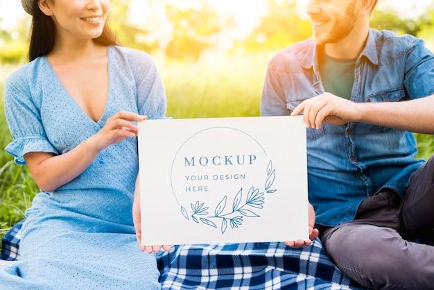 ピクニックのモックアップを保持しているカップル