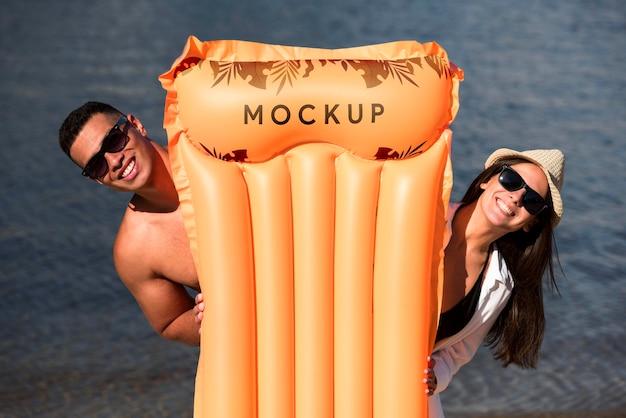 Couple holding a sea mattress
