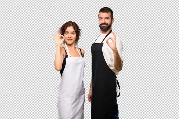 Пара поваров, показывая знак с пальцами