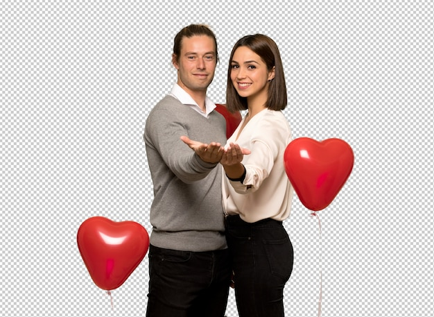 Couple in valentine day holding copyspace imaginary on the palm to insert an ad